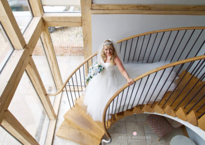 bride on stairs showing her wedding make up by pretty please by katie at cooling castle barn